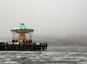 Carousel closed for winter on deserted pier, over a river that has iced over.